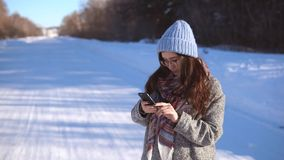 Girl in the winter forest near the road reading news in her mobile phone. stock footage