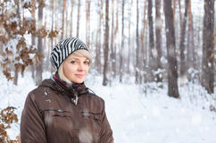 Girl in winter forest during a snowfall. Stock Photos