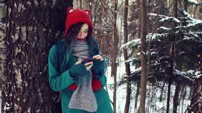 Girl in the winter forest is typing a message on the phone. The friendly girl in the beauty of knitted hat and coat in the winter snowy wood forest is typing a stock video footage