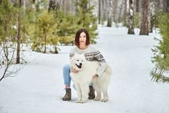 Girl in the winter forest walking with a dog. Snow is falling stock photo
