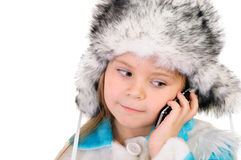 The girl in a winter fur cap speaks by phone Royalty Free Stock Photography