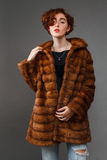 Girl in winter fur coat over gray background Royalty Free Stock Photography