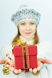 Girl in winter hat gives gift box Stock Photo