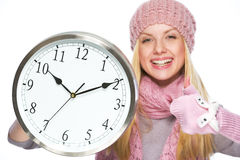 Girl in winter hat and scarf showing clock and thumbs up Stock Photos
