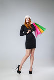 Girl in winter hat with shopping bags over gray Royalty Free Stock Image