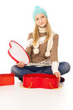 Girl in winter hat sitting with gift boxes Royalty Free Stock Image