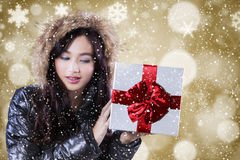 Girl with winter jacket holds gift box Stock Photos