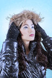 Girl in winter jacket stare copyspace. Beautiful young asian girl wearing jacket in snowy day and staring at copyspace royalty free stock photography