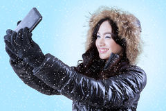 Girl with winter jacket taking picture. Smiling girl using a smartphone to take self picture while wearing winter jacket with blue background Royalty Free Stock Images