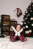 Girl in winter mittens from a Christmas tree Royalty Free Stock Photography