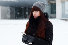 Girl in winter with a mobile phone Stock Photo