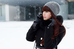 Girl in winter with a mobile phone Stock Image