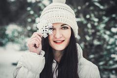 Girl portrait at winter outdoor, snowy weather, showing big snowflake toy. stock photography