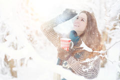 Girl in winter park with cup of hot drink Royalty Free Stock Photography