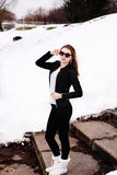 Girl in winter park in sunglasses and jacket Royalty Free Stock Photo