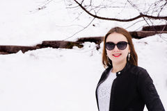 Girl in winter park in sunglasses and jacket Royalty Free Stock Photos