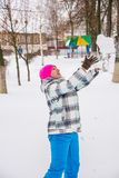 A girl in winter, playing in the snow, fun. Girl in winter plays in the snow in the Park outdoors having fun outdoors Royalty Free Stock Image