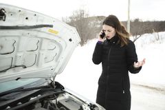 Girl on the winter road is calling the phone near the car royalty free stock photo