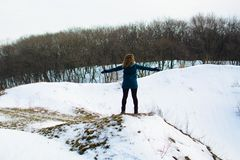 Girl in winter stands on a hill with his hands up. concept of freedom or victory royalty free stock photos