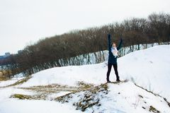 Girl in winter stands on a hill with his hands up. concept of freedom or victory royalty free stock photography