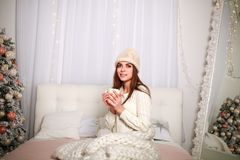 Girl in winter sweater and hat in warm blanket at home on bed. Girl in a winter sweater and a hat in warm blanket at home on a bed with a cup of coffee in the Royalty Free Stock Photo