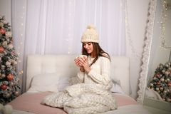 Girl in winter sweater and hat in warm blanket at home on bed. Girl in a winter sweater and a hat in warm blanket at home on a bed with a cup of coffee in the Royalty Free Stock Image