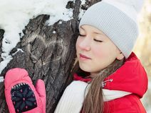 A girl in winter at tree with closed eyes Stock Images