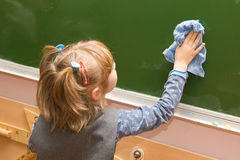 The girl wipes a blackboard. The schoolgirl washes a blackboard with a rag in a classroom Royalty Free Stock Images