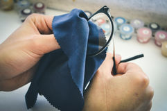 Girl wipes glasses with napkin. Girl wipes glasses with microfiber napkin royalty free stock images