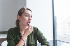 Girl wipes her lips with a napkin after eating at the restaurant. Portrait of a girl who wipes her mouth after eating. A pretty girl wipes her lips with a napkin royalty free stock photos
