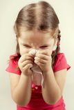 Girl wipes her nose with a tissue Stock Photo