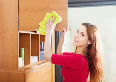 Girl wiping the dust from wooden furniture Royalty Free Stock Photo