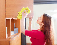 Girl wiping the dust from wooden furniture Royalty Free Stock Image