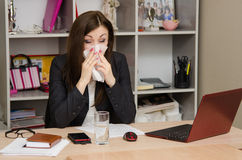 The girl wiping nose with a tissue in the office Royalty Free Stock Photo