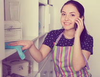 Girl wiping shelves and speaking on phone Stock Images
