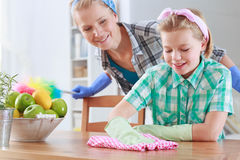 Girl wiping a table and her mum watching her. Happy little girl wiping a wooden table and her mom watching her Stock Photo