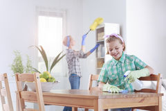 Girl wiping the table. Smiling girl wiping the table in a dining room Stock Photo