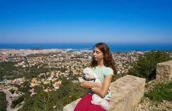 Girl wirh pet dog looking at Denia aerial view. In alicante of Spain royalty free stock photo