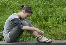 Girl wishes. Brunette young girl sitting on bench stock photos