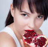 Girl wit garnet. Brunette girl with garnet fruit in studio royalty free stock photos