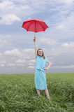 Girl wit red umbrella in meadow Stock Image