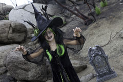 Girl in witch attire trying to scare you while standing in cemetery Stock Photos