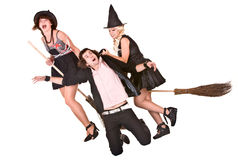 Girl witch on broom and helpless man. Two girl witches on brooms with helpless man. Isolated Stock Photography