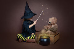 Girl in witch costume casting spell on teddy bear Royalty Free Stock Photo