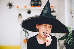Girl in Witch costume eating soft jelly candy Stock Images