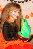 Girl in witch costume Halloween kissing a frog Royalty Free Stock Images