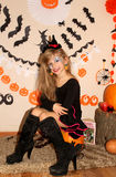 Girl in witch costume on Halloween on the pumpkin Stock Image