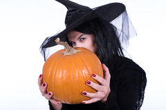 Girl in the Witch Costume Holding Big Pumpkin Royalty Free Stock Photography