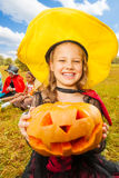 Girl in witch costume holds pumpkin with hands Stock Image