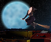Girl witch fly over city against moon and star sky Stock Photo